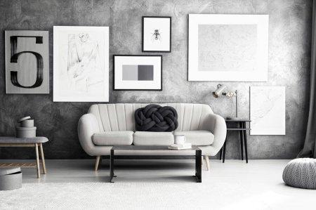Foto de Almohada de oscuro nudo en un sofá junto a la mesa en el interior de la acogedora sala de estar con galería de carteles de pared de hormigón - Imagen libre de derechos