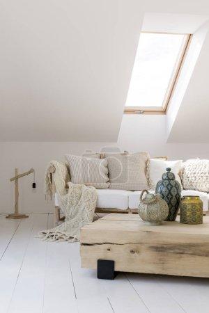 Photo pour Lampe conçue sur le sol à côté du canapé beige avec couverture en tricot dans le salon avec vases ethniques sur une table en bois - image libre de droit