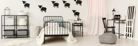 Photo for Patterned pouf and white ladder next to a desk with laptop and lamp in teenager's bedroom interior with black bed - Royalty Free Image