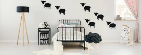 Photo for Wooden lamp and black nightstand next to bed in contrast color bedroom interior for a kid with knot pillow on stool - Royalty Free Image