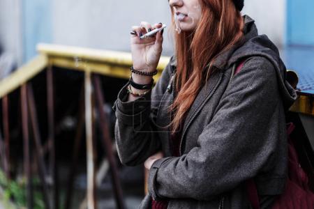 Photo pour Photo recadrée d'un adolescent roux fumant une cigarette à l'extérieur - image libre de droit