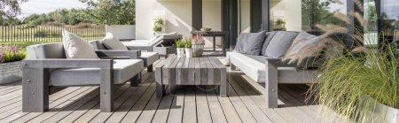 Photo pour Terrasse en bois avec mobilier design dans grande résidence - image libre de droit