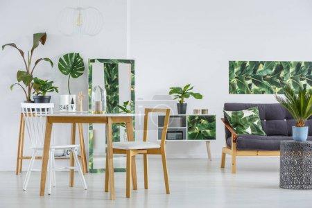 Photo pour Intérieur blanc et moderne de la salle à manger avec canapé noir et décorations botaniques - image libre de droit