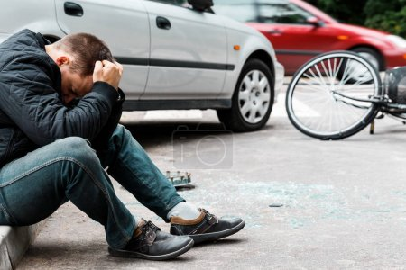 Photo for Man sitting on the sidewalk and crying after causing a car accident - Royalty Free Image