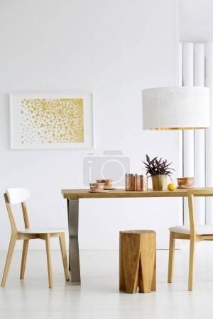 Photo pour Cuivre bols sur la table dans la salle à manger confortable intérieur avec peinture or et tabouret en bois - image libre de droit