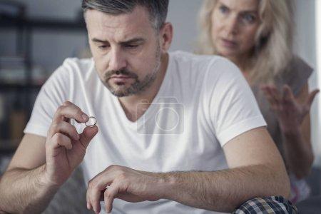 Photo pour Triste mari tenant son alliance après s'être disputé avec sa femme jalouse - image libre de droit