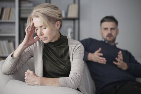 Photo pour Femme déprimée et fatiguée avec un mal de tête au milieu d'un conflit avec un mari jaloux - image libre de droit