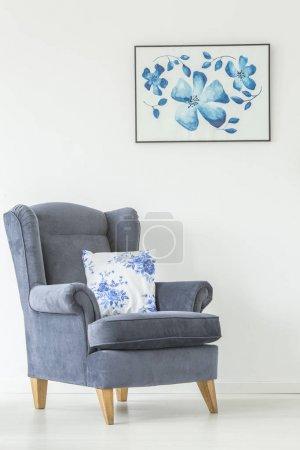Photo pour Coussin floral sur fauteuil contre un mur blanc avec affiche de fleurs dans le salon lumineux intérieur - image libre de droit