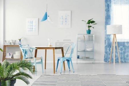 Foto de Foto borrosa de un amplio comedor interior con planta de palma de pie en el suelo junto a la alfombra a rayas - Imagen libre de derechos