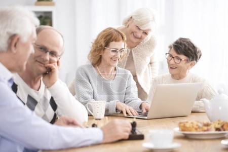 Photo pour Des aînés heureux parlent, surfent sur Internet et boivent du café ensemble dans une maison de retraite - image libre de droit
