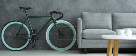 Photo for A blue bike standing in a grey living room interior next to a sofa and white table with wooden legs - Royalty Free Image