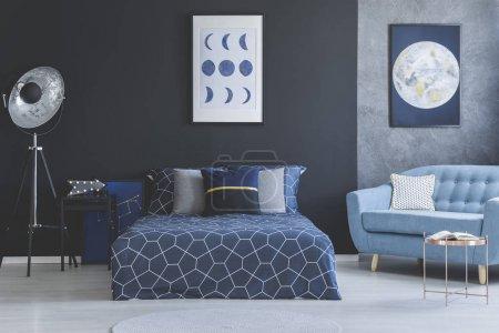 Photo pour Canapé bleu dans la chambre à coucher intérieur avec lit bleu marine contre mur sombre avec galerie d'affiches - image libre de droit