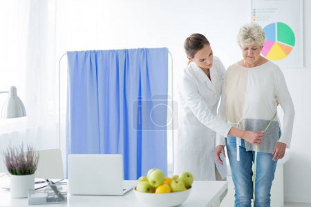 Dietician measuring woman's body circuit