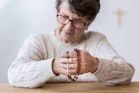 Photo pour Contemplant la femme âgée, prier avec le chapelet rouge dans l'église - image libre de droit