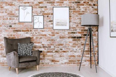 Photo pour Oreiller à motifs gris fauteuil et lampe contre le mur de briques rouges avec des affiches à l'intérieur de la salle de séjour - image libre de droit