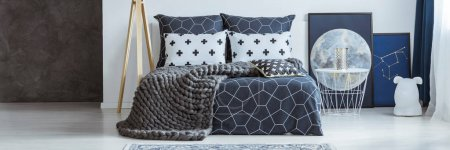 Photo for Knit wool blanket on patterned bed in bedroom interior with white table and moon poster - Royalty Free Image