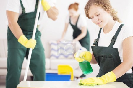 Photo for Female worker holding a table cleaner in one hand and a soft cloth in the other - Royalty Free Image