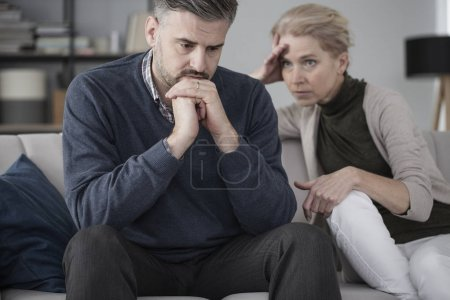 Photo for Worried husband and wife sitting in marriage therapy with focus on the sad man in the foreground - Royalty Free Image
