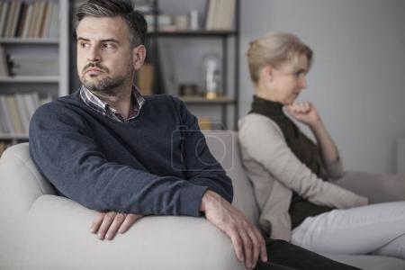 Photo pour Hommes et femmes assis sur un canapé blanc séparément après une querelle - image libre de droit