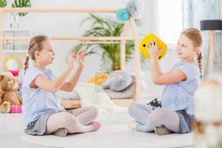 Photo pour Sœurs jumelles souriantes jouant avec des dés jaunes en peluche dans la salle de classe - image libre de droit