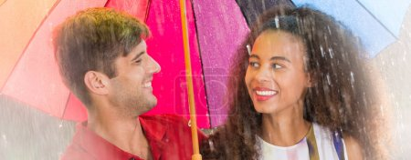 Photo for Multicultural couple looking each other in the eyes during summer stroll - Royalty Free Image