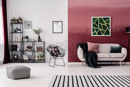 Photo for Metal chair and grey sofa with blanket and two pillows standing in living room interior with burgundy wall - Royalty Free Image