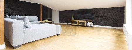Photo pour Spacieux, salon intérieur vide avec canapé d'angle gris support TV en bois et murs en briques - image libre de droit