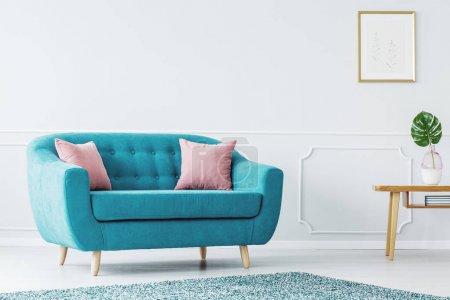 Foto de Sofá color turquesa y rosa cojines sobre un suelo blanco de madera de un interior de diseño minimalista sala de estar con paredes blancas con espacio de copia - Imagen libre de derechos