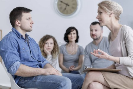 Photo for Upset man sitting in group therapy and listening to the psychologist with concerned family in the background - Royalty Free Image