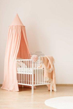 Foto de Cuna minimalista, blanco con un dosel rosa pastel para una niña por una pared blanca, vacía en un interior de sala vivero lindo y moderno - Imagen libre de derechos