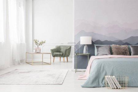 Photo pour Table basse moderne cadre doré avec un vase en verre élégant et confortable fauteuil vert dans un intérieur blanc studio avec grand lit - image libre de droit