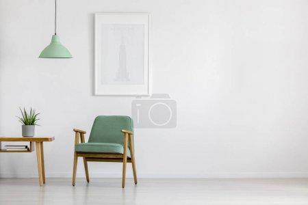 Foto de Retro, menta Sillón, mesa de madera y cartel enmarcado en un brillante interior minimalista con espacio de copia - Imagen libre de derechos