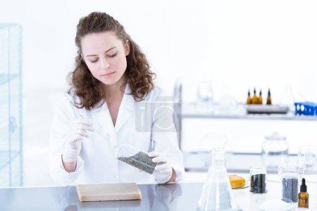 Photo pour Scientifique travaillant avec des substances chimiques dans un laboratoire blanc - image libre de droit