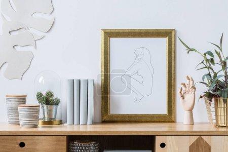 Foto de Plantas, libros y adornos con elementos de oro de una situación interior de moda y moderno salón blanco en muebles de madera - Imagen libre de derechos