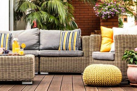 Yellow pouf on wooden terrace