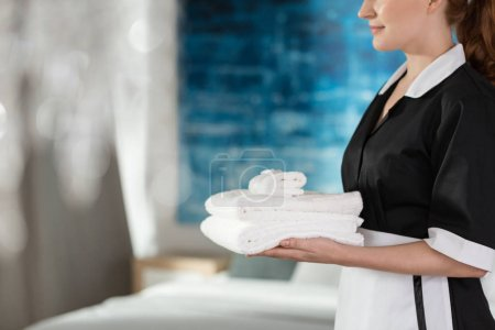 Photo for A young, smiling housemaid holding fresh, washed towels - Royalty Free Image