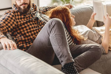 Photo for Couple lying together on sofa and relaxing during the weekend - Royalty Free Image