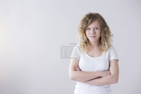 Portrait of a young woman in white t-shirt, with curly blonde hair with her arms crossed on an empty background