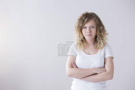 Photo pour Portrait d'une jeune femme en t-shirt blanc, aux cheveux blonds bouclés les bras croisés sur fond vide - image libre de droit