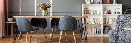 vier graue Stühle stehen an einem Spitzentisch im Esszimmerinnenraum mit Leseecke