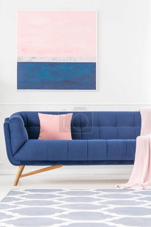 Photo for Navy blue couch with pink pillow and blanket in living room interior with patterned carpet and painting on the wall - Royalty Free Image