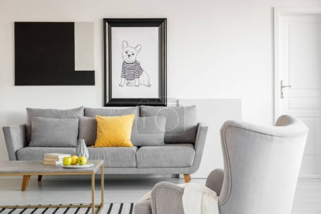 Photo for Big comfortable wing back armchair next to long grey scandinavian sofa with pillows in bright living room interior - Royalty Free Image