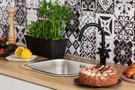 Photo pour Gâteau, herbes et fruits sur le comptoir de cuisine dans l'intérieur lumineux de la cuisine avec des carreaux à la mode sur le mur - image libre de droit