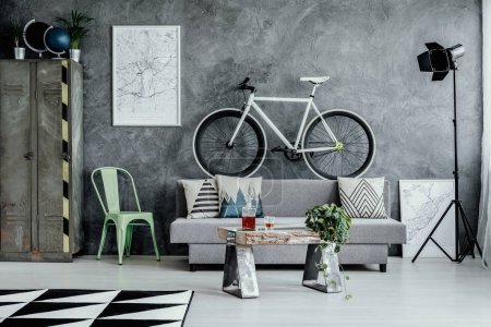 Photo for Mint green metal chair next to grey sofa with pillow in dark living room interior with map on empty concrete wall and industrial furniture - Royalty Free Image