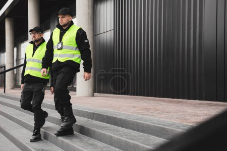 Photo pour Les policiers en gilets réfléchissants regardant attentivement autour pendant la patrouille dans le centre-ville - image libre de droit