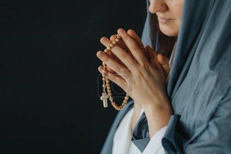 Photo pour Gros plan de la Mère de Dieu priant en tenant un chapelet - image libre de droit