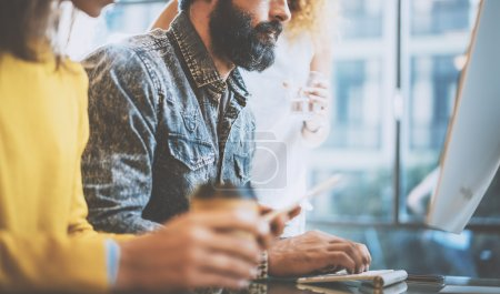 Bearded man typing on desktop keyboard in a sunny office near the windows. Young coworkers discussing business ideas at workplace.Horizontal,blurred background.