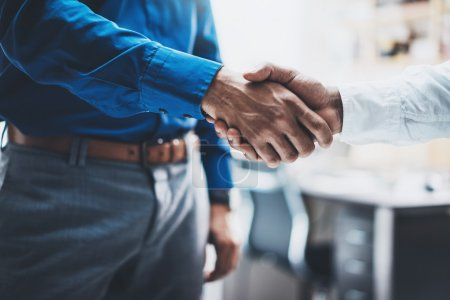 Business partnership handshake concept.Photo of two businessmans handshaking process.Successful deal after great meeting.Horizontal, blurred background.