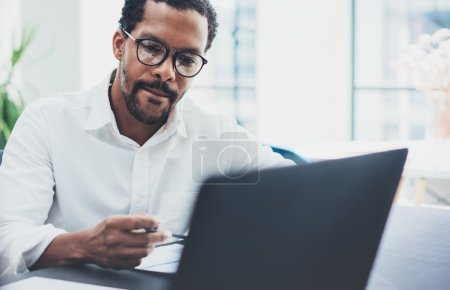 Dark skinned coworker wearing glasses and using laptop in modern office.African american man in white shirt working on workplace.Horizontal,blurred background
