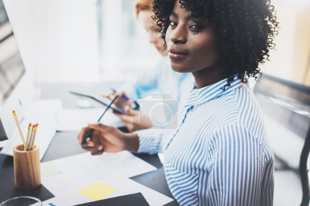 Young attractive african woman smiling and looking at the camera in modern office.Coworkers teamwork concept. Horizontal, blurred background.